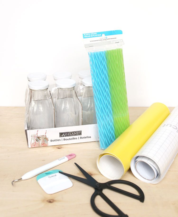 Craft supplies on a wooden background: scissors, plastic straws, vinyl, Cricut tools, and glass milk bottles