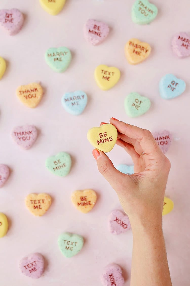 Yellow, orange, blue, and green conversation heart Valentine's Day bath bombs in a hand on a pink background
