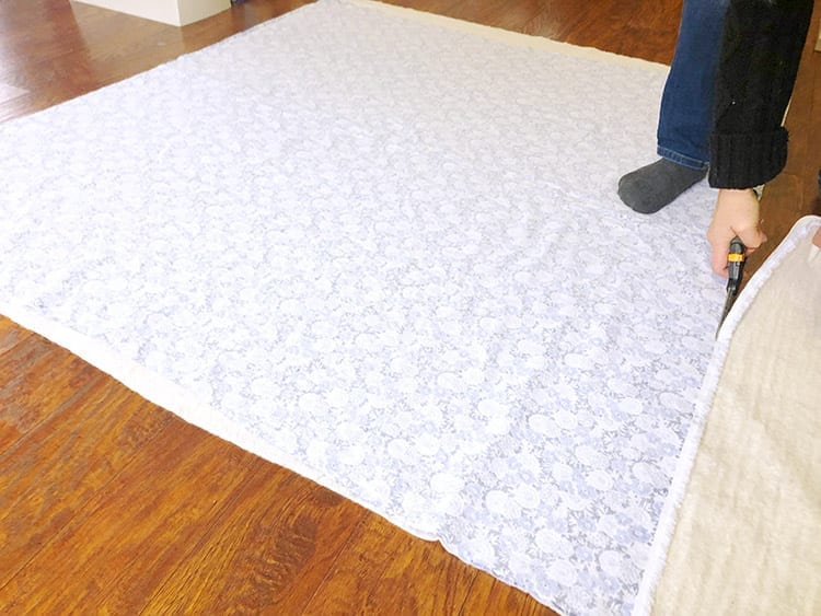 Person's hand cutting sheet of fabric on a wood floor