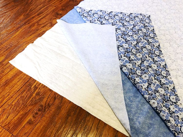 Three sheets of fabric layered on top of each other on a wood floor