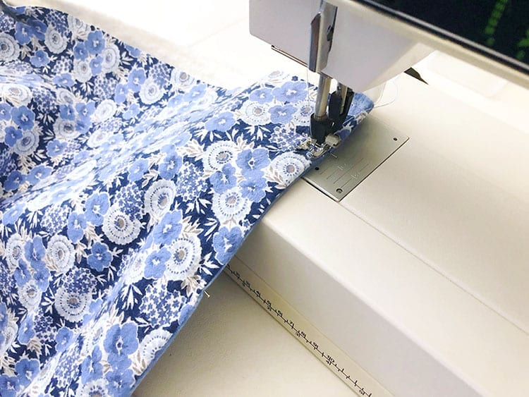 Sewing machine sewing a straight stitch on blue floral fabric
