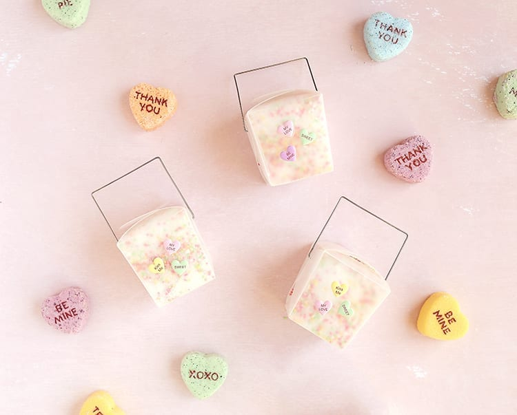 Clear takeout containers of valentines day bath salts on a pink background with giant conversation hearts