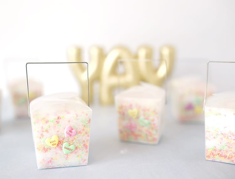 Clear takeout containers filled with conversation hearts Valentine's Day bath salts recipe on a grey background in front of a YAY sign in gold letters