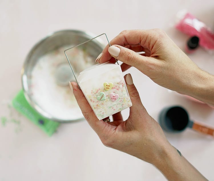 Caucasian hands holding a clear takeout container with conversation hearts stickers and containing a Valentine's Day bath salts recipe mixture