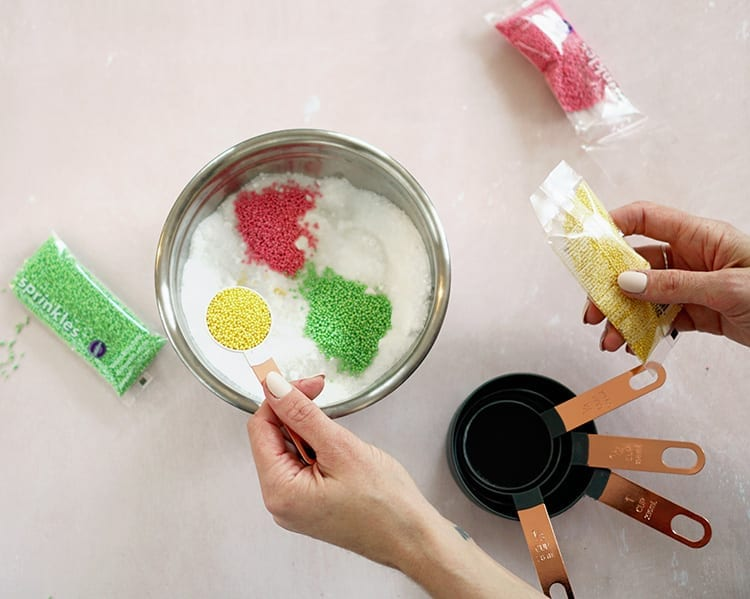 Caucasian hand pouring a spoonful of yellow sprinkles into a metal mixing bowl on a pink background