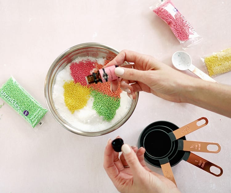 Hand adding a drop of cotton candy scented oil to Valentines Day bath salts recipe mixture in a metal bowl on a pink background