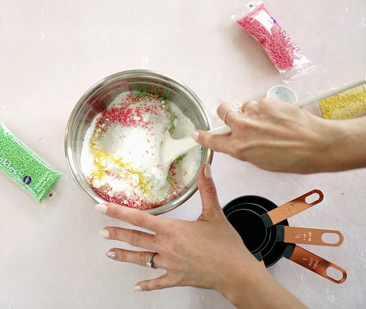 Caucasian hand mixing Valentine's Day bath salts recipe in a metal bowl with a white spoon over a pink surface