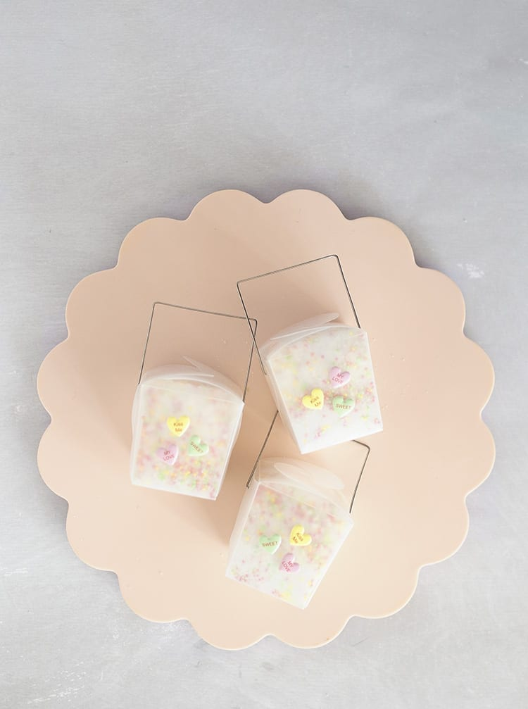 Three clear takeout containers with conversation hearts stickers on a pink scalloped tray on a grey background
