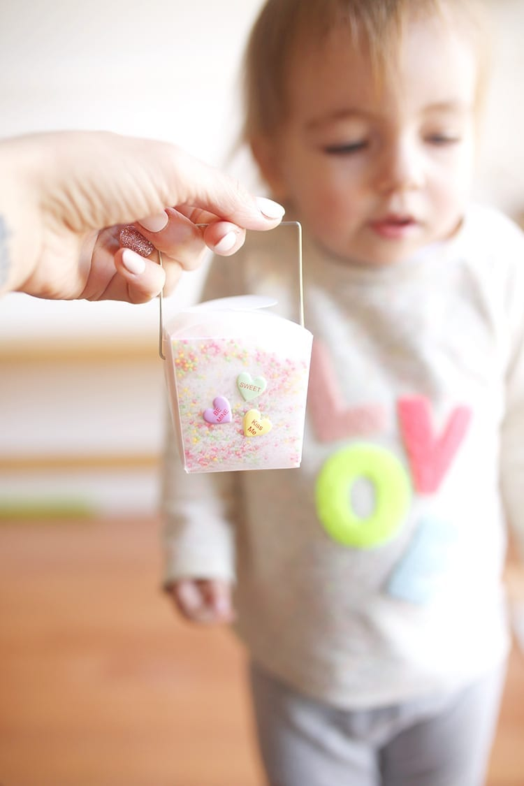 Hand holding a clear takeout container of Valentine's Day bath salt recipe in front of a baby wearing a sweatshirt that says LOVE
