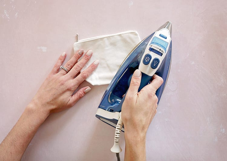 Caucasian hand ironing a small white canvas pouch against a pink background