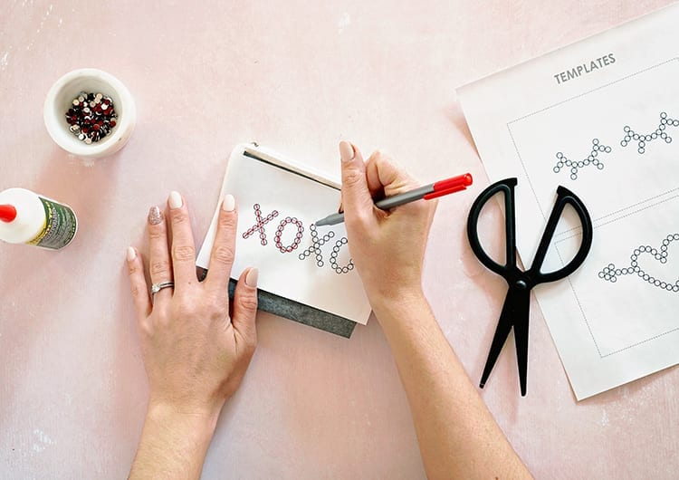 Caucasian hands tracing XOXO template with red pen on white paper against a pink background