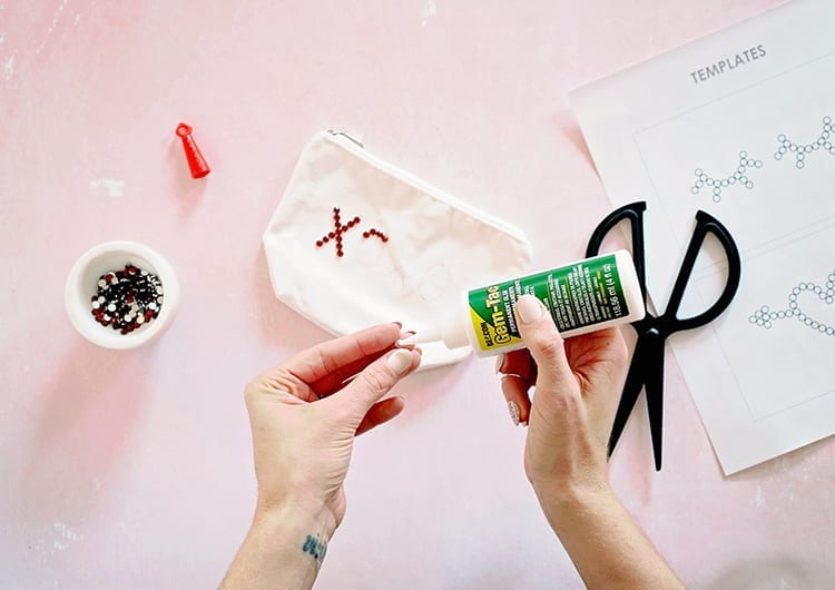 Hands applying Beacon Adhesives Gem-Tac to a red rhinestone against a pink background