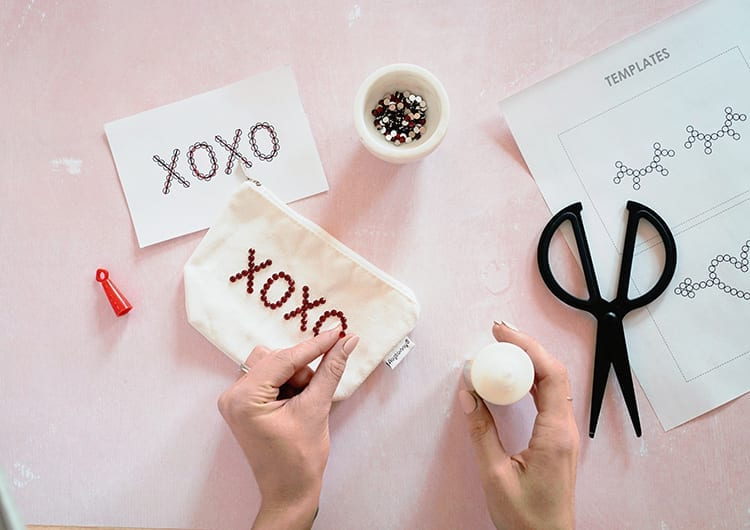 Hands applying a red rhinestone to an XOXO design on a white canvas pouch against a pink background