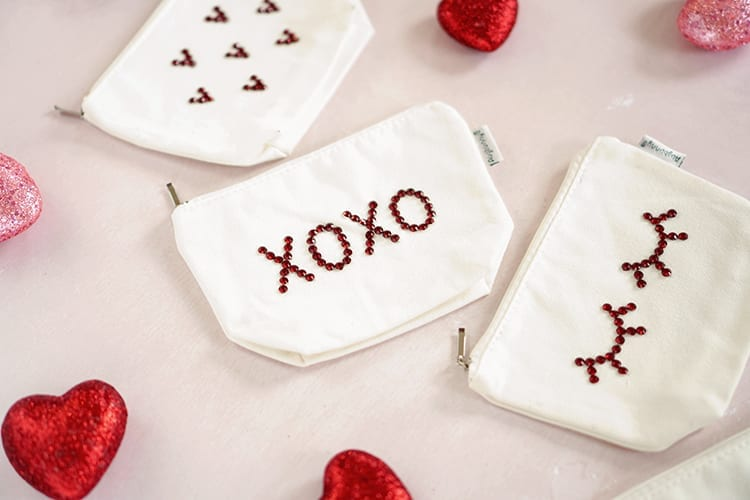 Four white canvas pouches with red rhinestone assorted designs. Lying on a pink background with pink and red glitter hearts scattered around