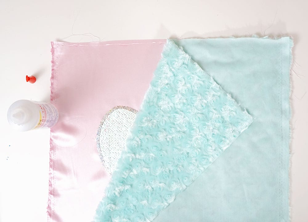 Turquoise faux fur fabric on top of reversible sequin fabric heart and pink satin to make a mermaid sequin pillow