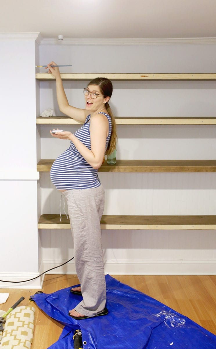 Pregnant Caucasian woman with long brown hair in blue and white striped tank top paints light blue paint on wall on front of shelves being installed
