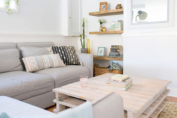 White living room with light grey sectional sofa, whitewashed wooden pallet coffee table, and wooden floating shelves