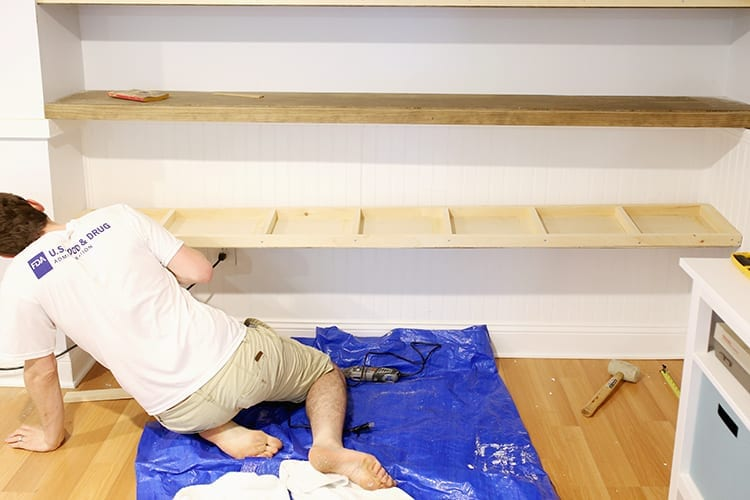 Man installing a pine shelf frame onto a white wall over a blue tarp