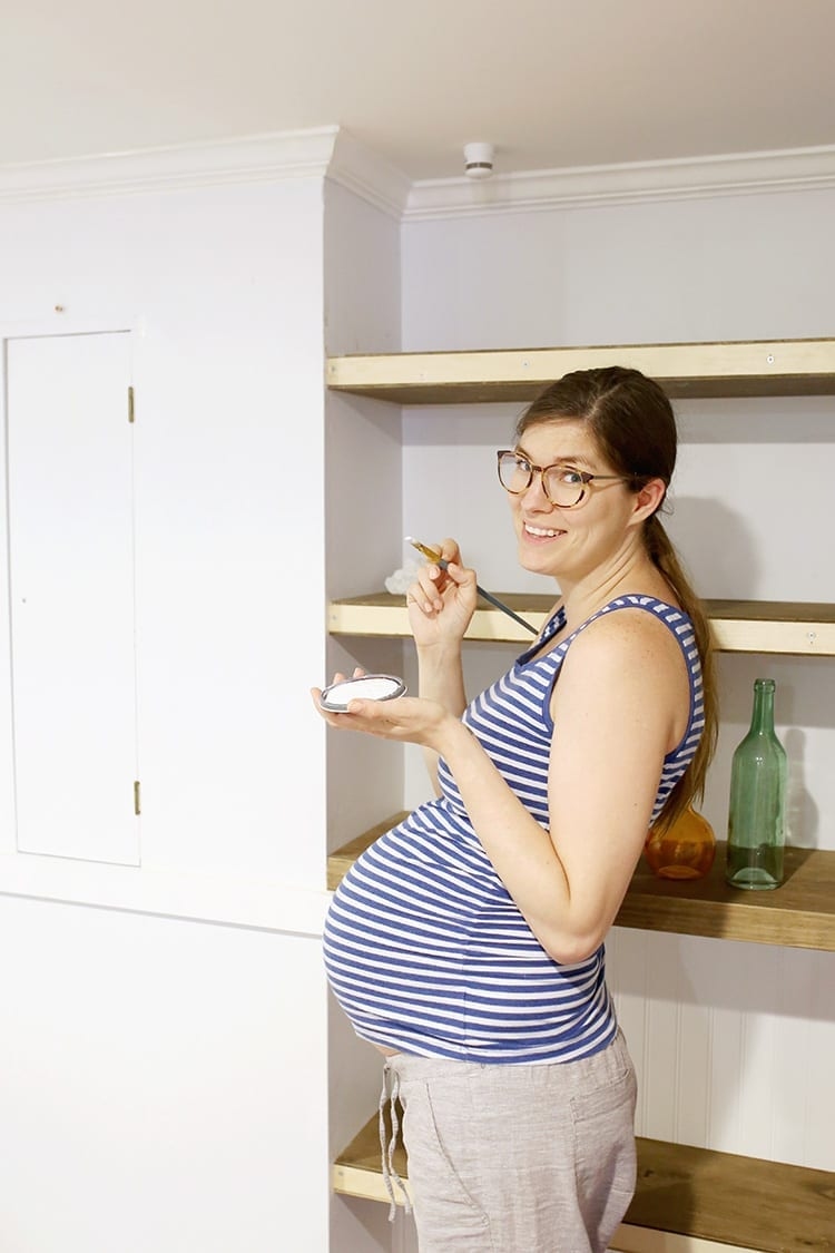 Pregnant Caucasian woman with long brown hair in blue and white striped tank top paints light blue paint on wall