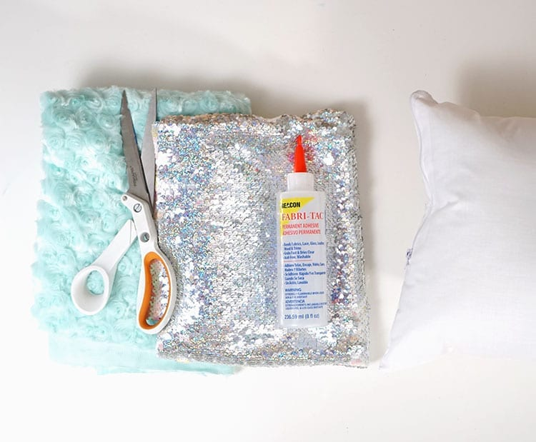Fabric, sewing scissors, Beacon Adhesives Fabri-Tac glue, and pillow insert for magic sequin pillow