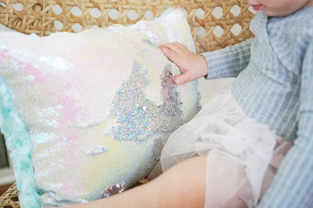 Toddler hands playing with a pink heart shaped mermaid sequin pillow