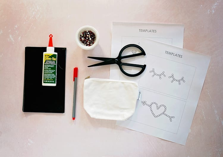 Beacon Adhesives Gem-Tac glue, graphite transfer paper, black scissors, a small white canvas pouch, a dish of red rhinestone, and white printouts on a pink background