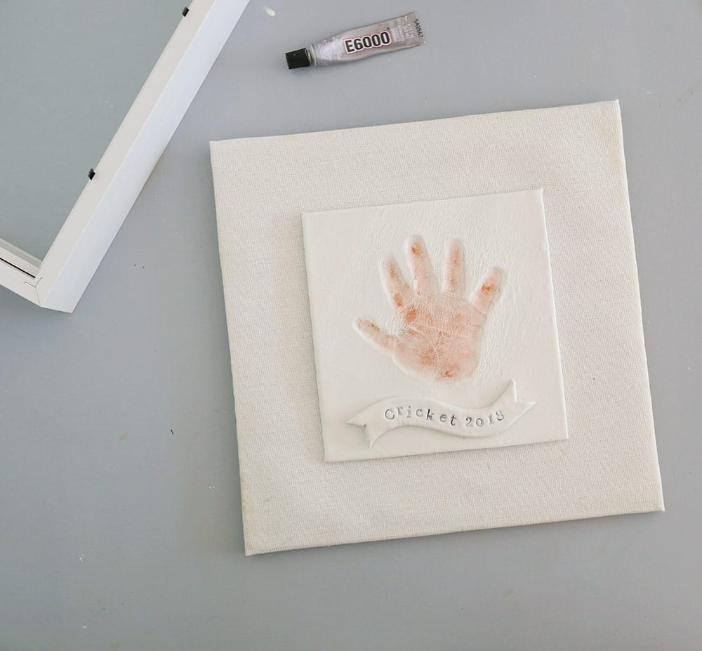 Copper hand print in air dry clay on a silicone baking mat to make a diy baby clay handprint keepsake frame