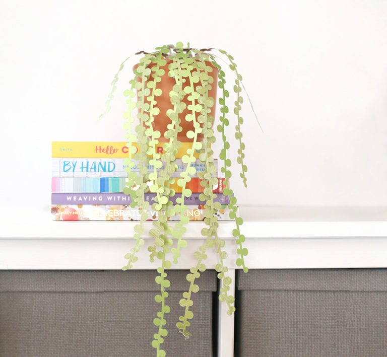 String of pearls DIY paper succulents in a terra cotta pot against a white wall