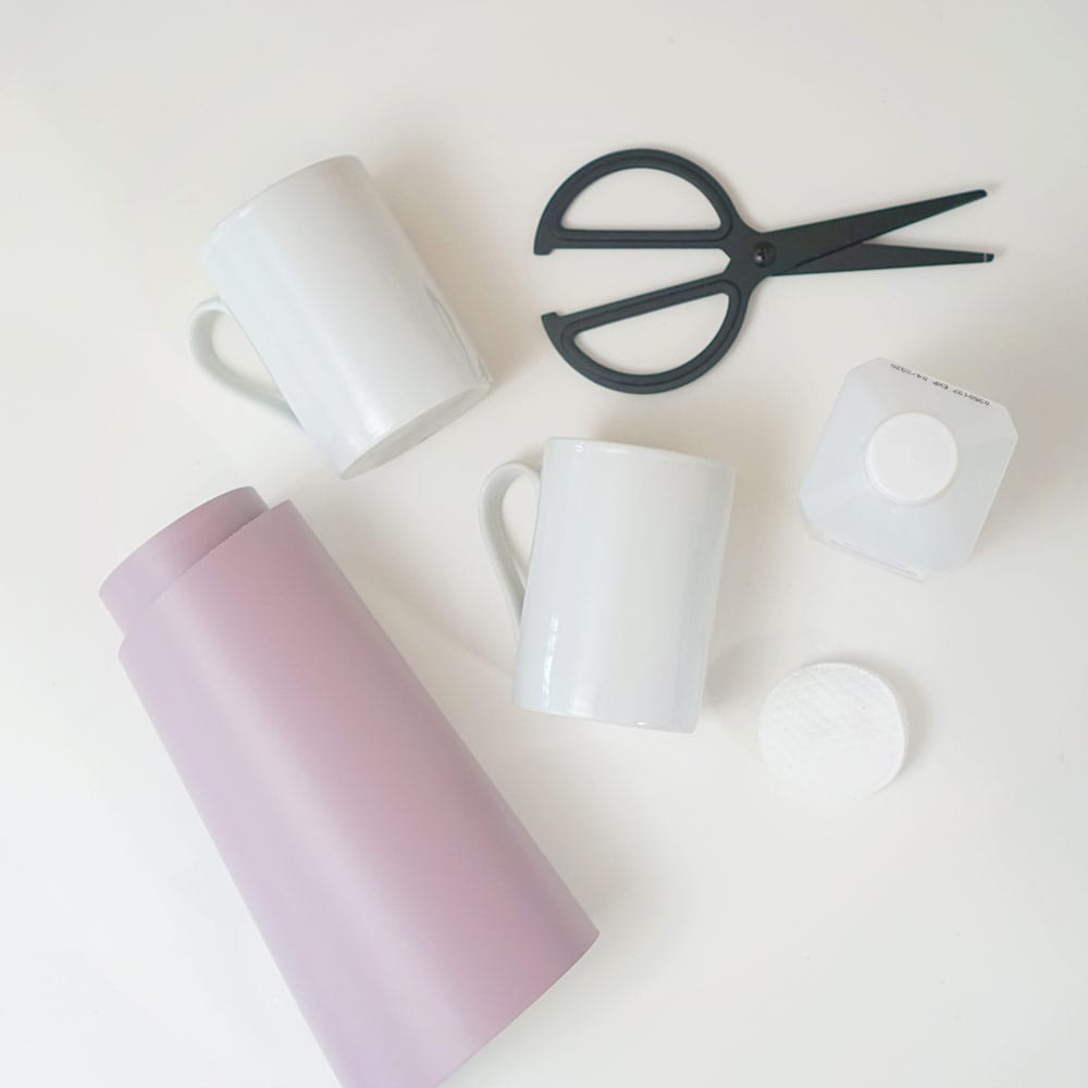 Lavender vinyl, black scissors, and white coffee cups on a white background for DIY wine mugs