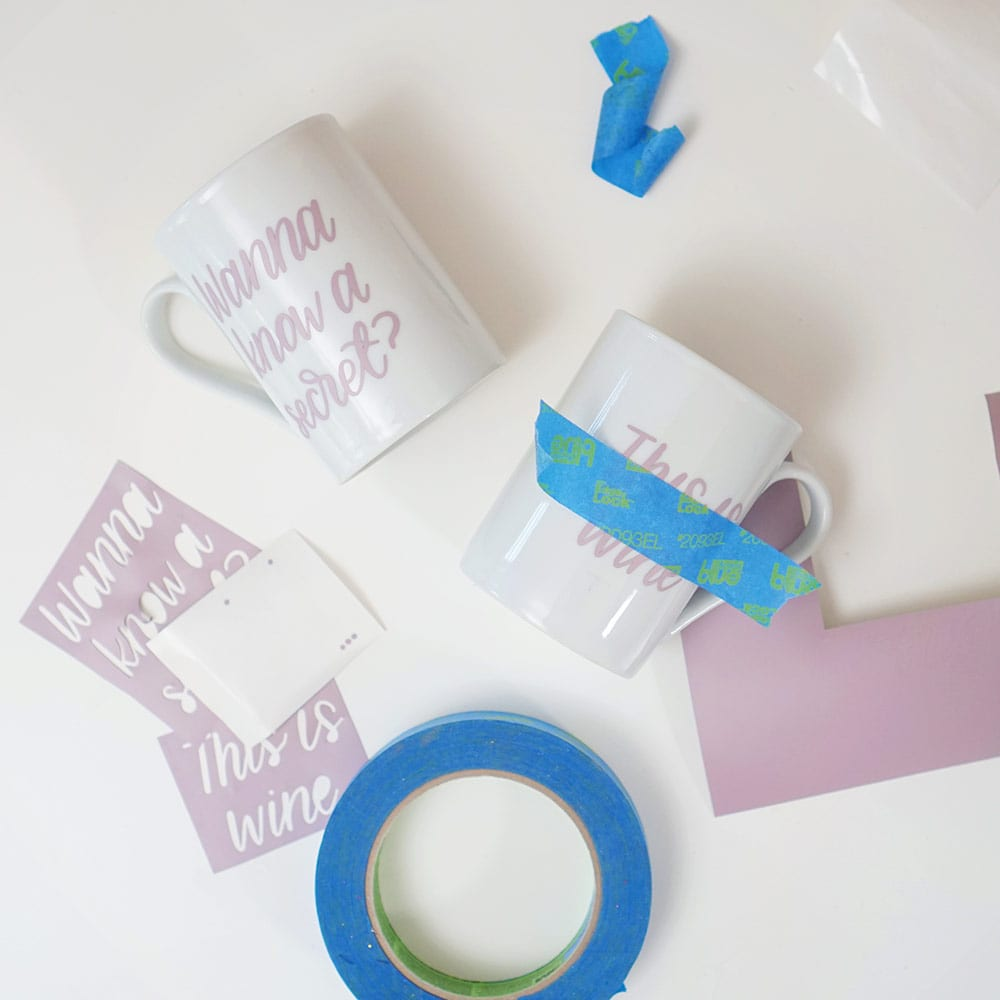 Lavender vinyl, blue tape, and white coffee cups on a white background for DIY wine mugs