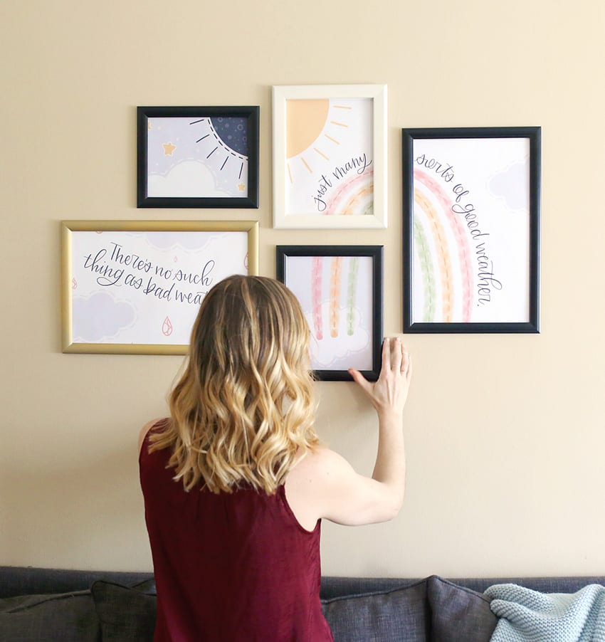 Woman with blonde ombre balayage hair puts a frame on a gallery wall