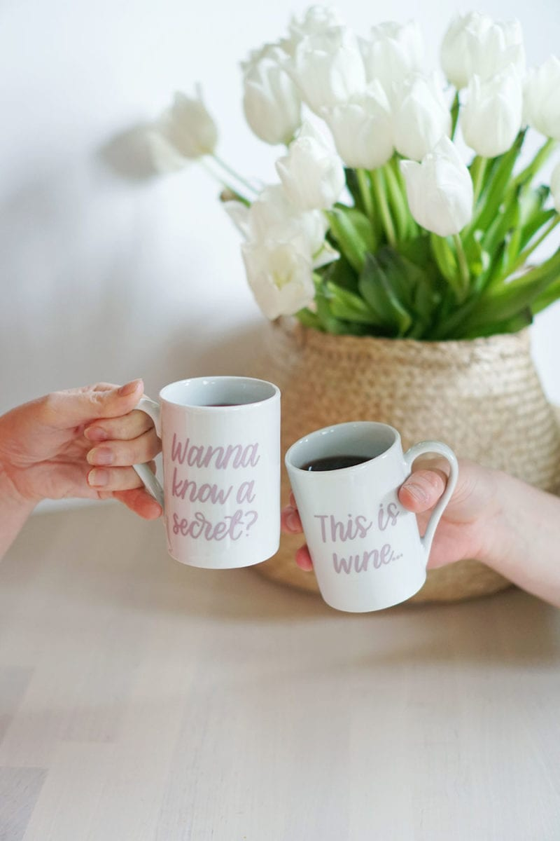 Two hands toasting with a set of this might be wine mugs