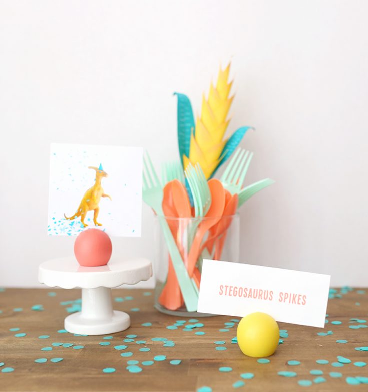 Dinosaur birthday party setup with yellow, coral, and teal accessories