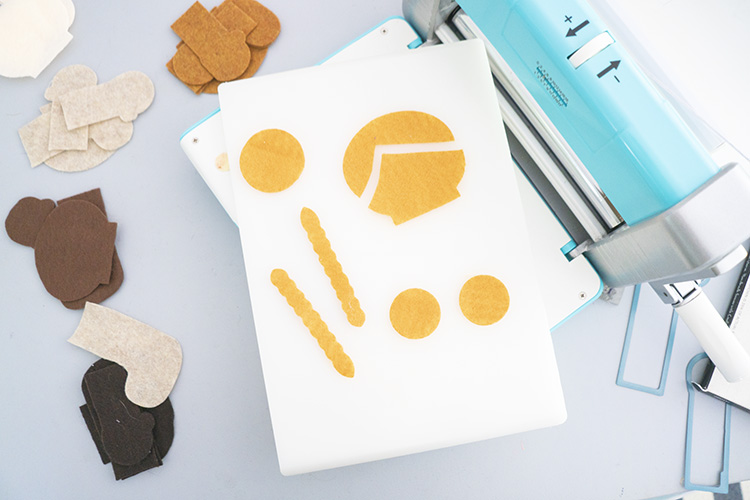 Crafter's Edge Crossover II machine with white plate and yellow felt shapes