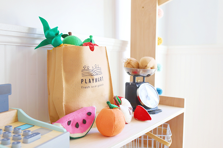Felt fruit and vegetables and a DIY play grocery bag that looks like a brown paper bag