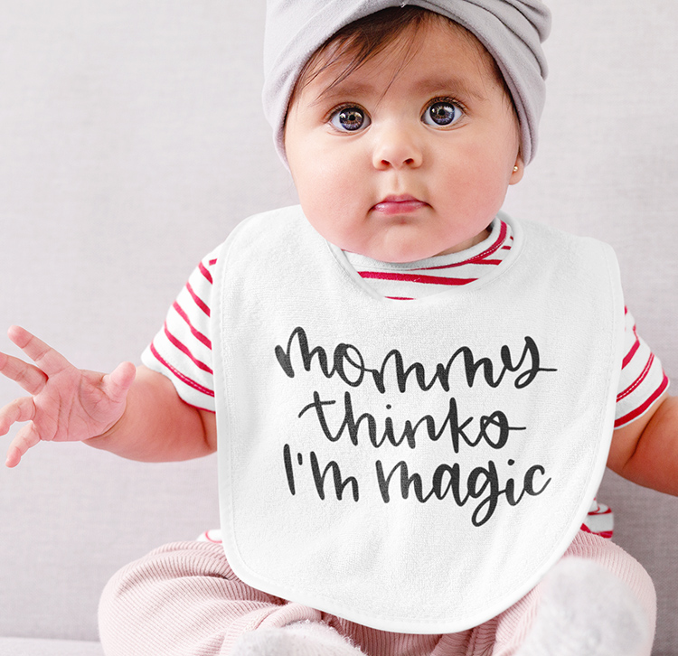 White baby with a white bib that has a free SVG cut file of Mommy Thinks I'm Magic