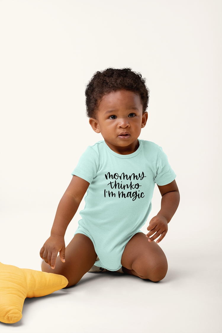 "Black baby in a light blue onesie that says ""Mommy Thinks I'm Magic"""