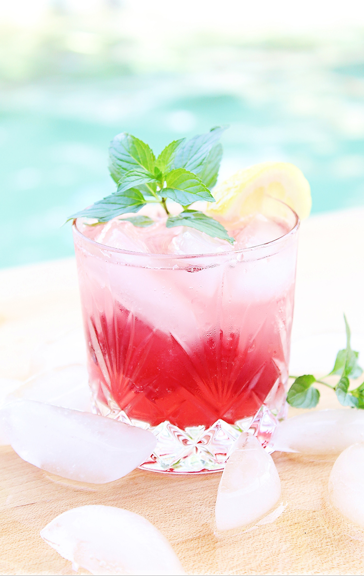 Cocktail in a rocks glass with cherry lemonade drink and a sprig of mint next to a pool for summer
